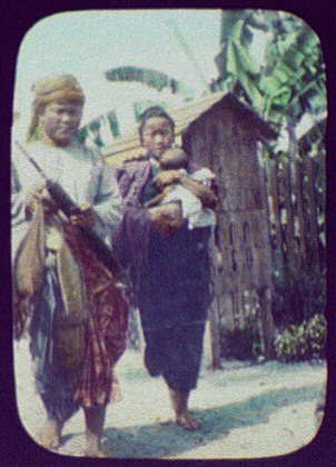 Man, woman, and child in front of small hut on stilts