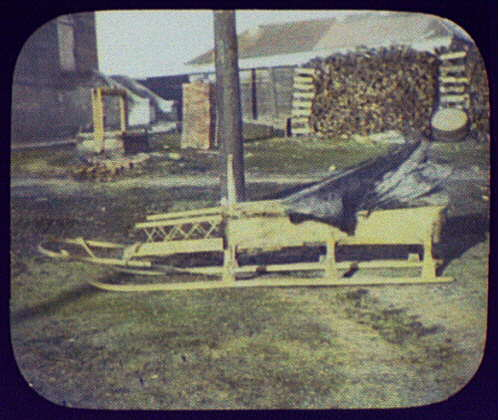 Siberian sledge; full side view with well and large woodpile in background