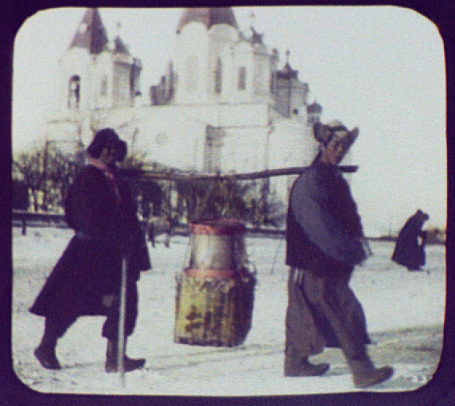Irkutsk (?) - 2 men (Mongols?) carrying load on pole between their shoulders; large church in background